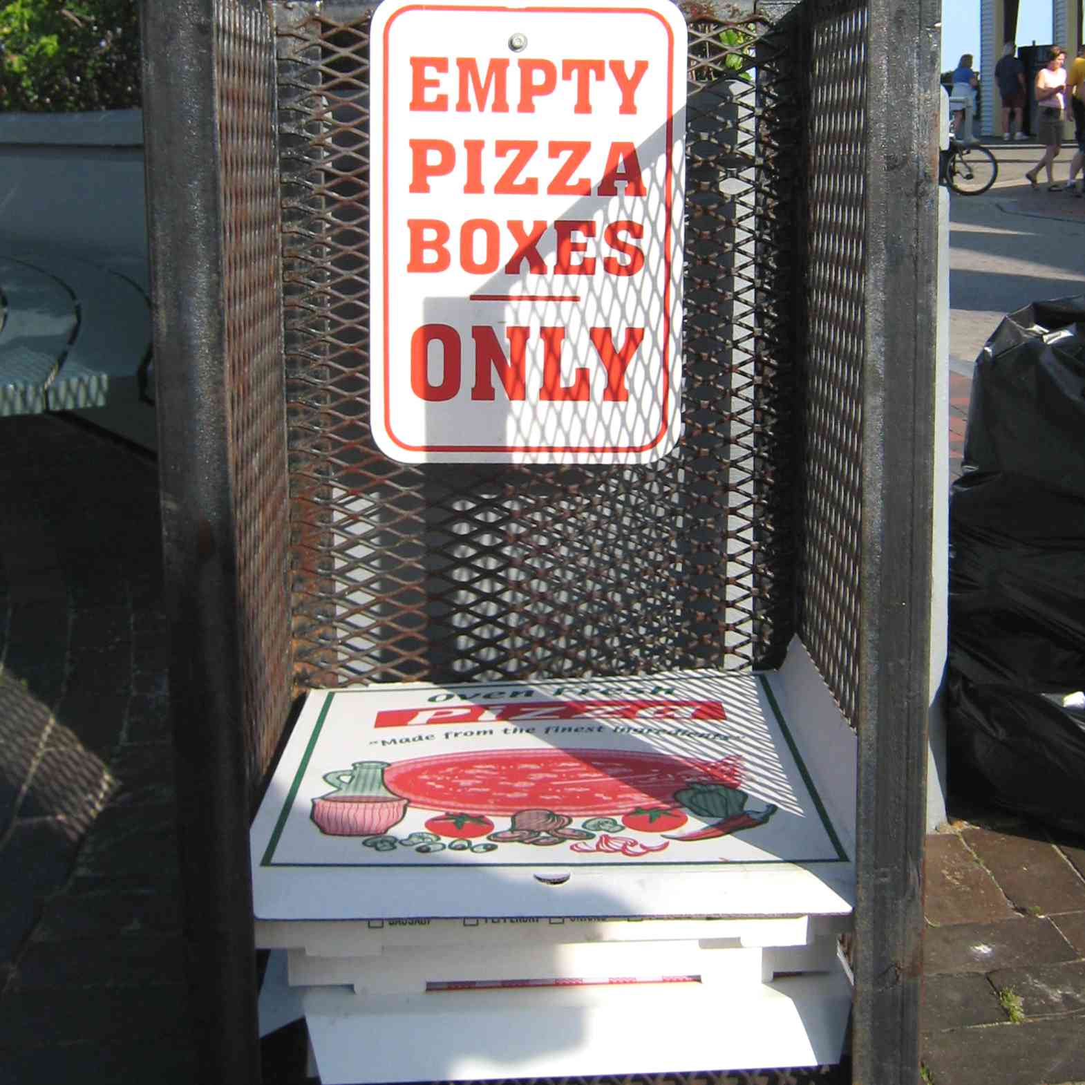 A metal crate for pizza box returns with sign saying empty pizza boxes only