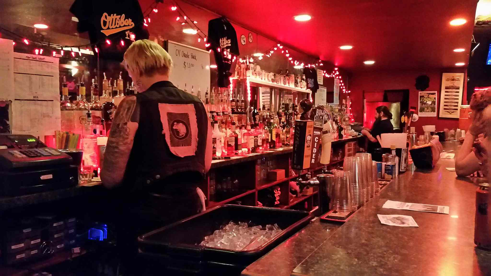 a red-lit bar at night with bartenders