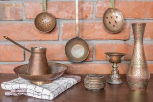shot of copper and brass cooking utensils against brick