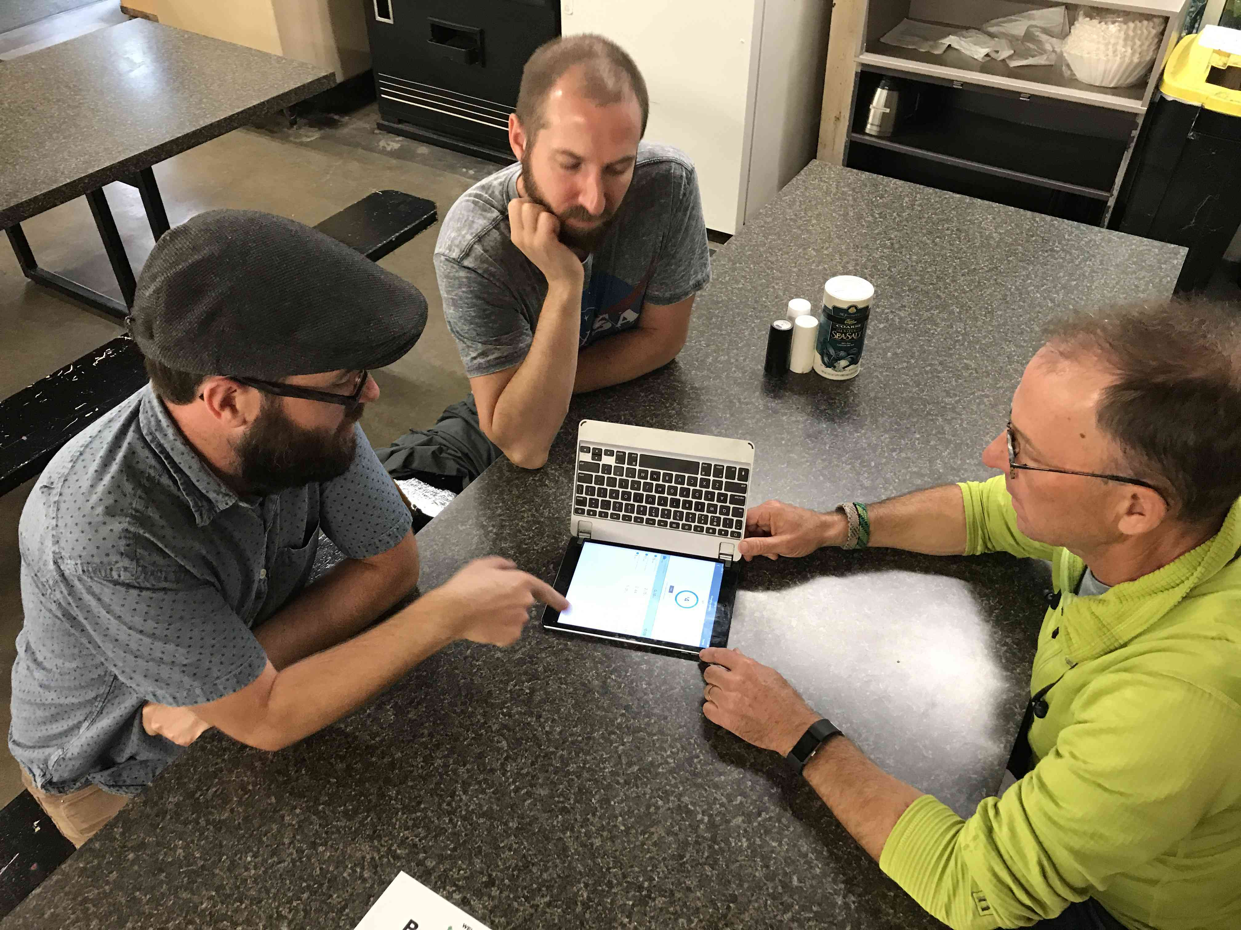 Three men meeting at a table with a tablet in between them