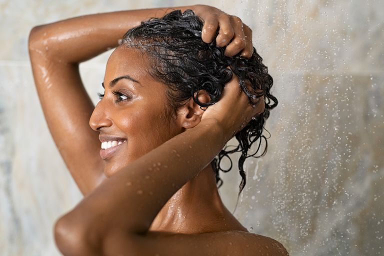 A black woman in the shower lathers her hair.