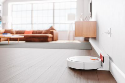 Robotic vacuum sitting in its charging dock next to a wall