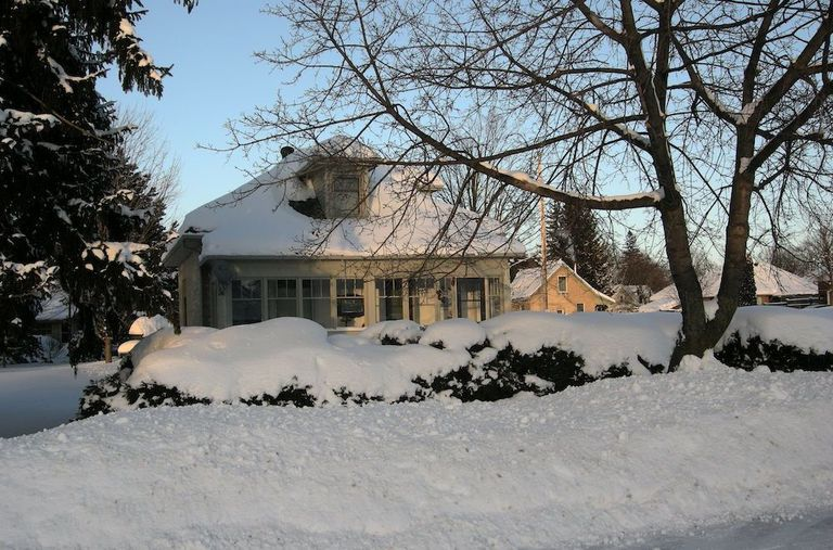 House in a wooded area after snow has fallen