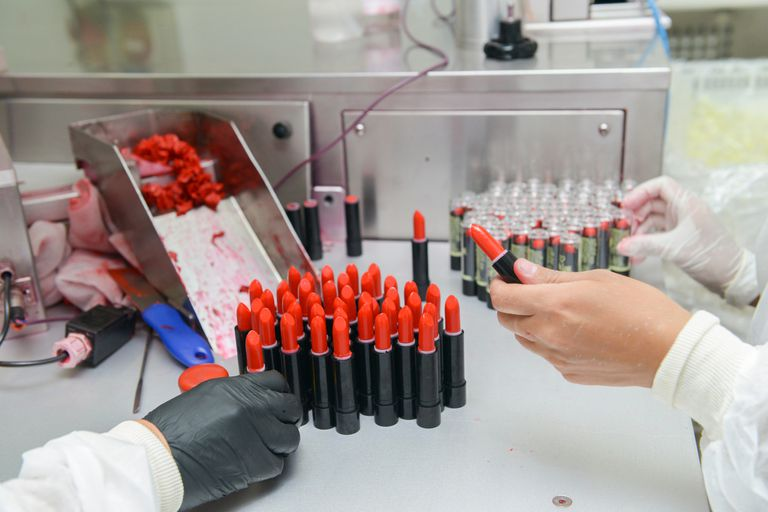 Cropped Hands Of People Making Lipstick In Factory