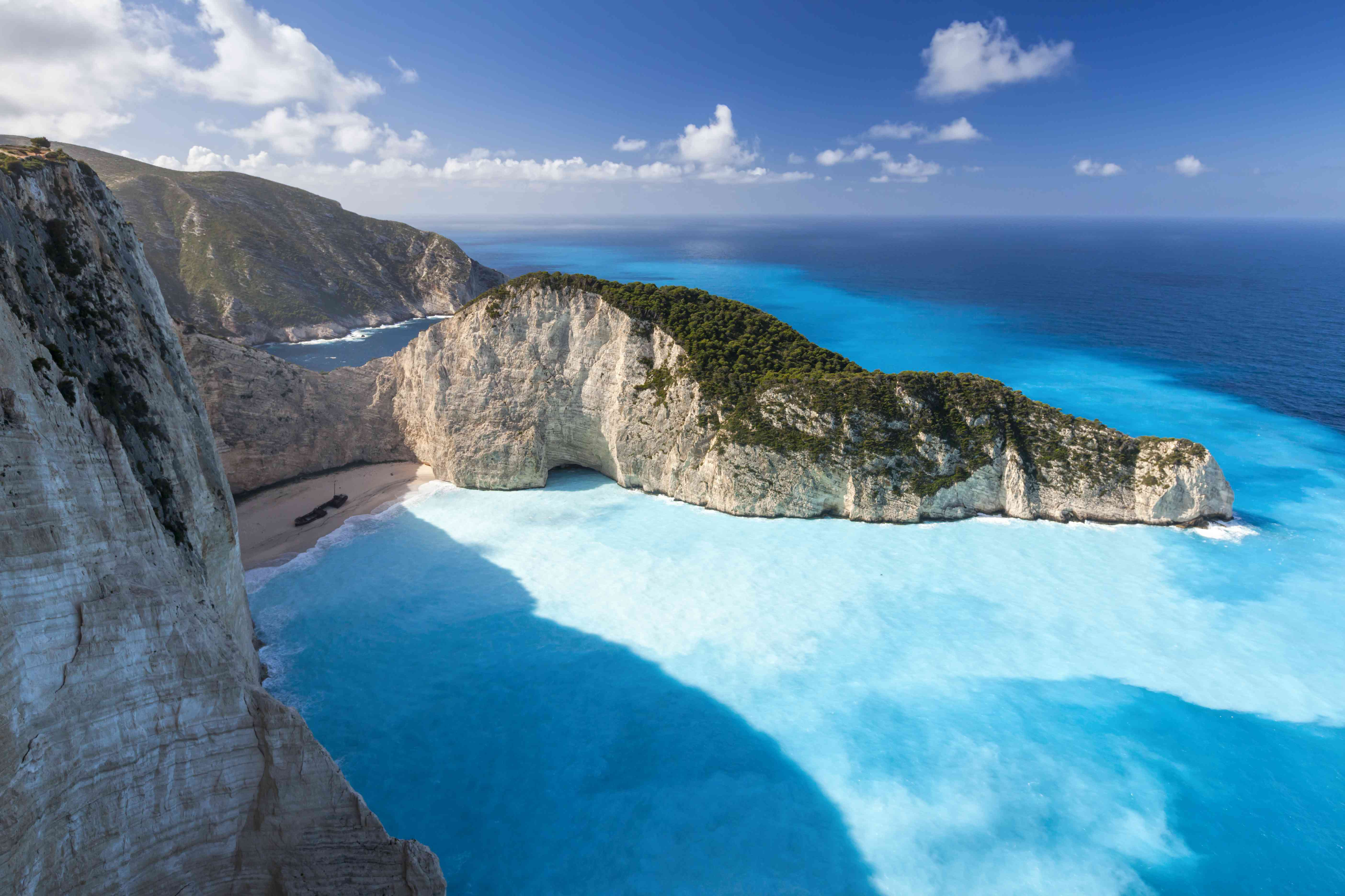 The white cliffs of Navagio Beach rise above the shipping vessel on the sand below with bright blue waters stretching to the horizon