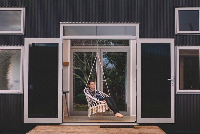 Woman sitting in the hanging chair with patio doors open to a small porch