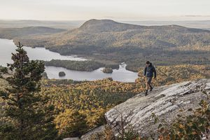 Hiker walking along cliff with view on Appalachian Trail, Maine