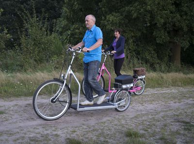 Man and woman traveling down a dirt path on treadmill bikes