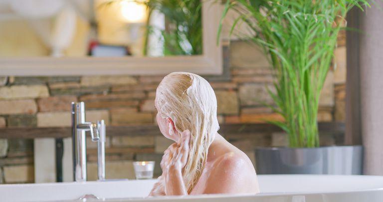 A blonde woman washing her hair in the bath tub.