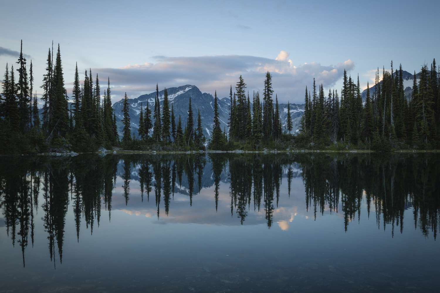 A tree-lined lake at sunrise at Mount Revelstoke National Park