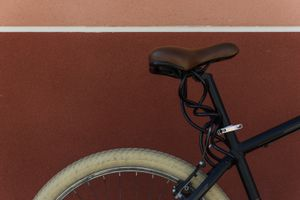 Black bike with brown seat against a dark red wall