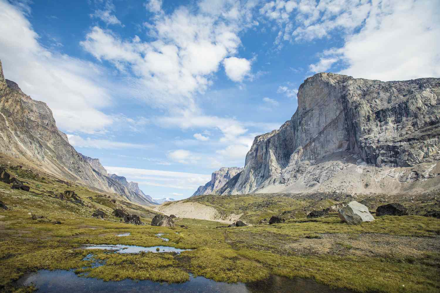Steep cliffs of Auyuittuq National Park look over a green valley