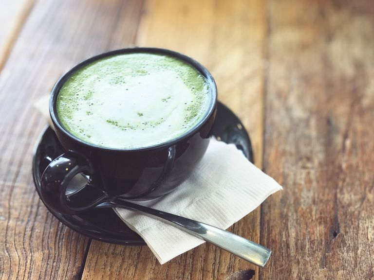 Matcha latte in a tea cup sitting on a wooden table