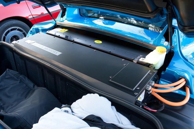 A black electric car battery in a bright blue car.