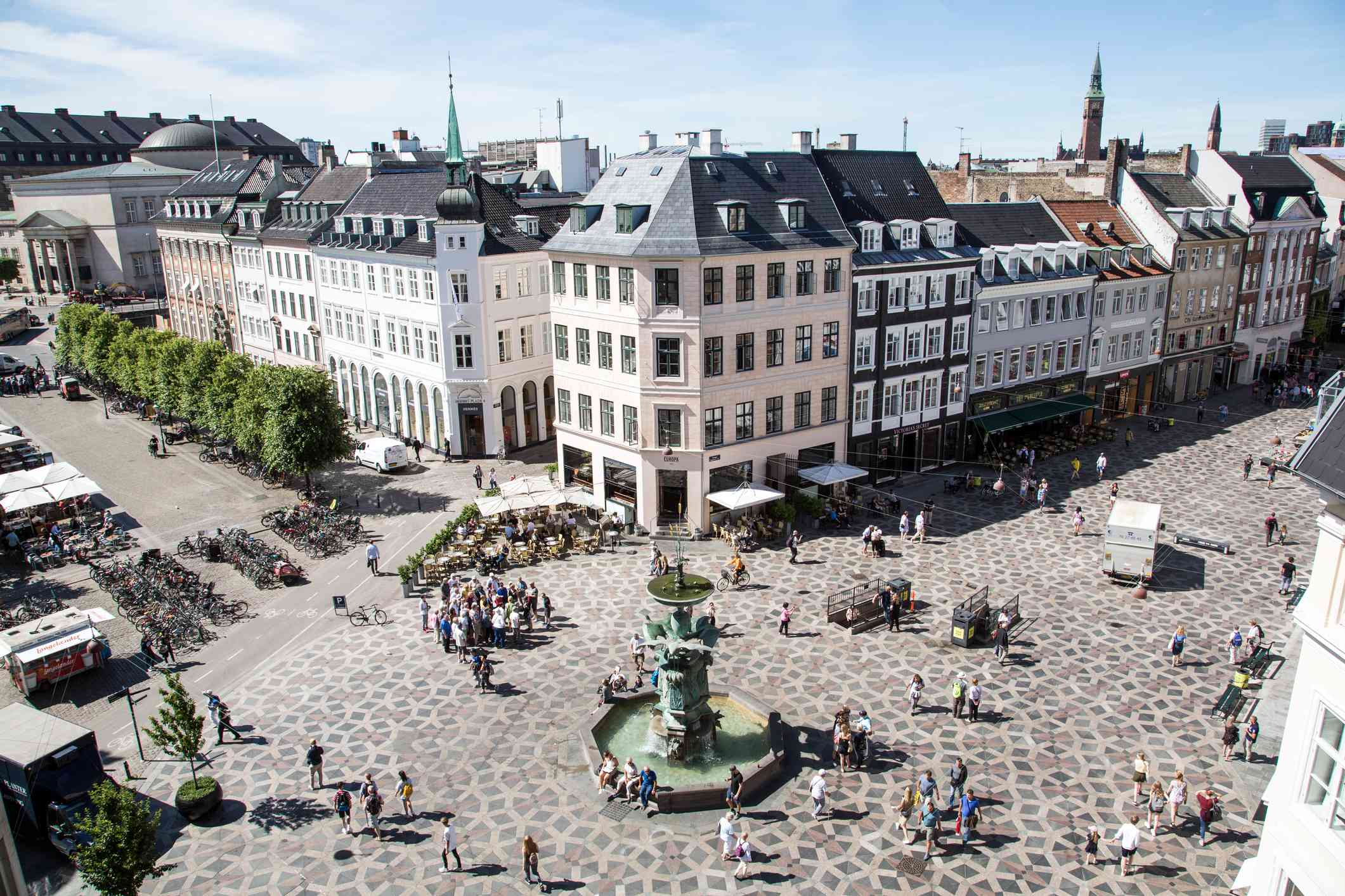 aerial view of a shopping area with wide, decorative tile walkways surrounding a green fountain at Strøget in Copenhagen