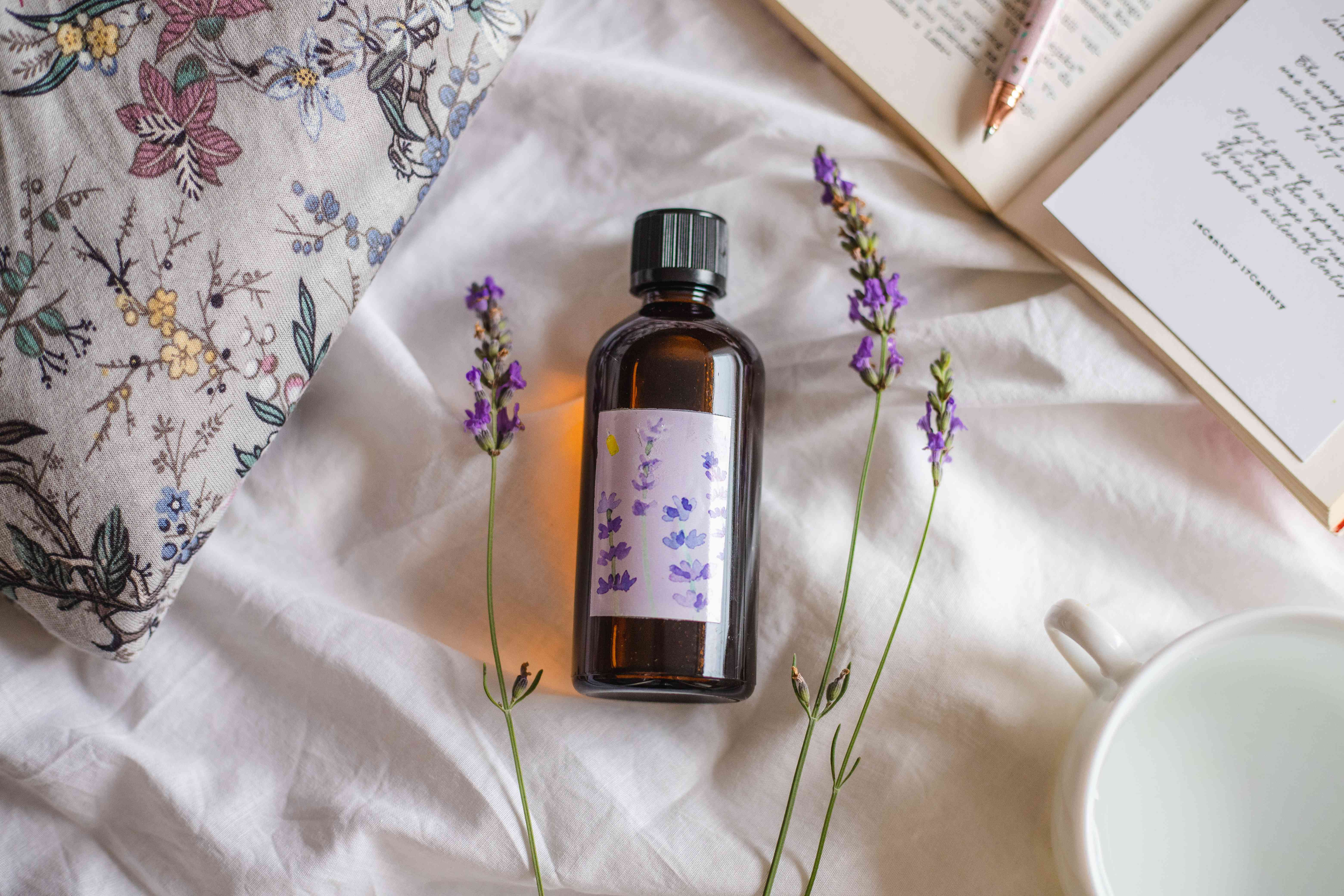 homemade amber bottle of lavender bottle oil arranged on fabric next to dried lavender and journal