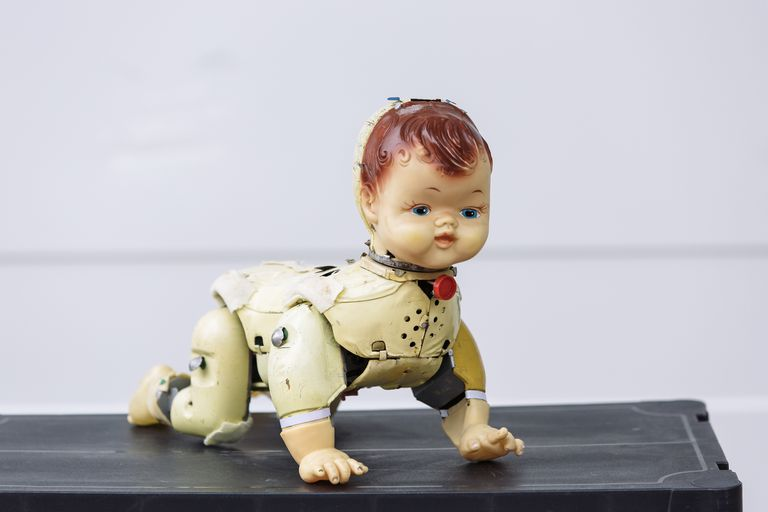 A vintage doll without clothes crawling on a surface.
