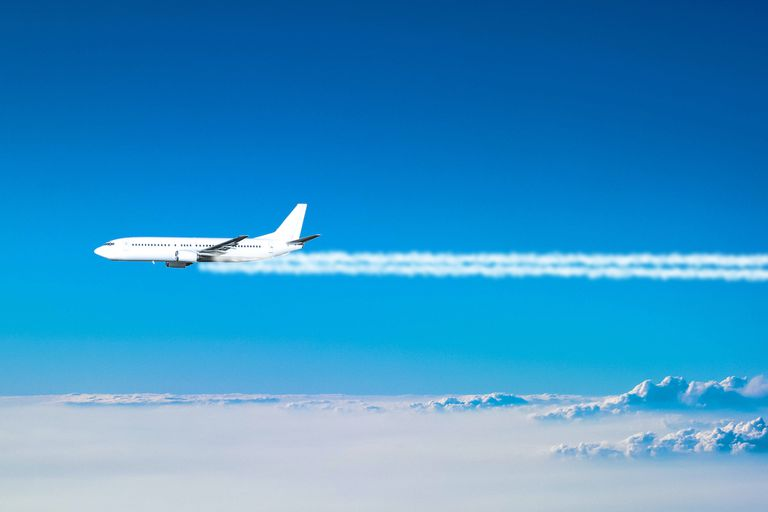 Airplane flying above the clouds leaving a smoke trail
