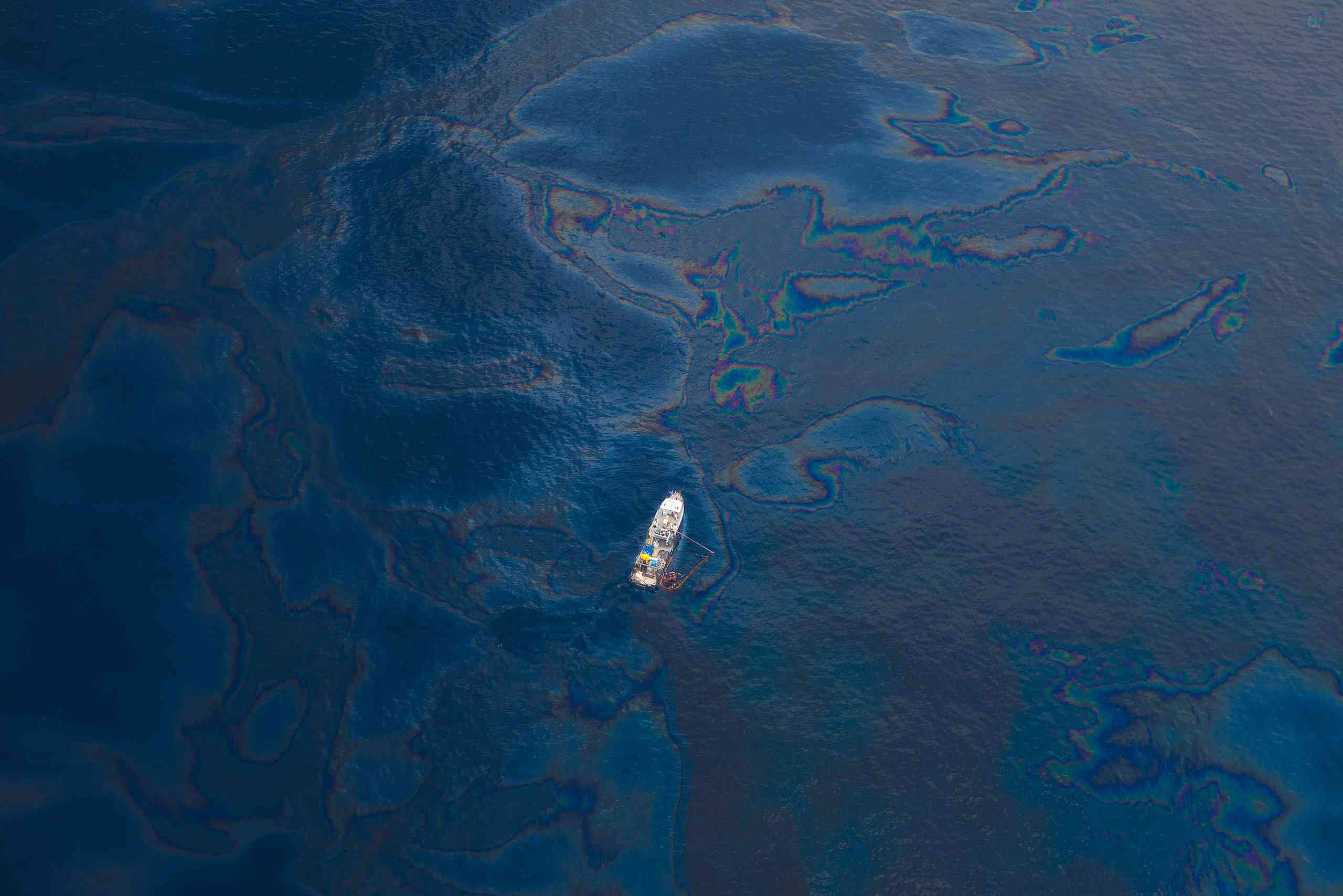 Aerial view of a lone boat in the Gulf of Mexico with oil visible on water's surface