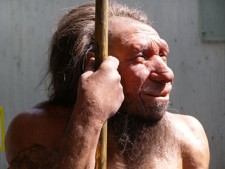 profile of neanderthal statue holding staff near face in sunlight