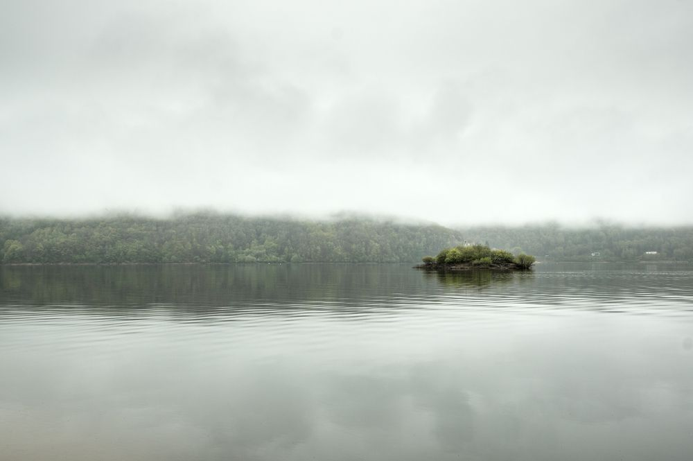 A small island stands out against a haze-covered lake.