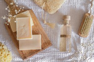 bars of soap and liquid castile soap display on white waffle fabric with wooden brush and loofah