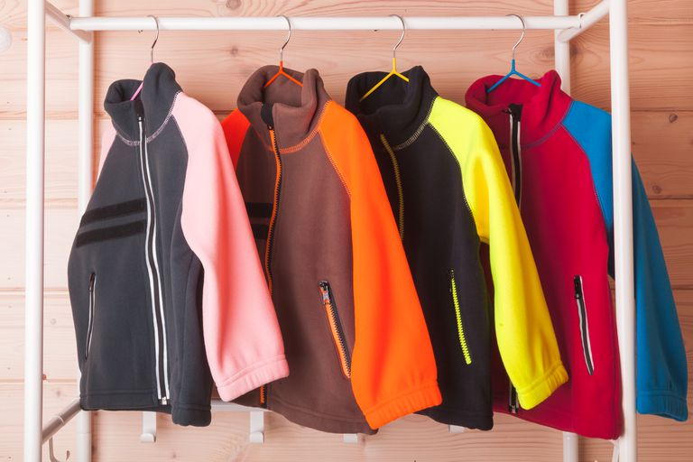 Colorful fleece jackets are hanging on hangers