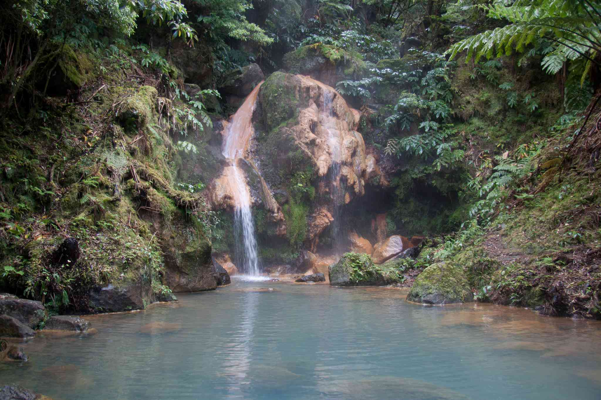 A waterfall flows into the hot springs at Caldeira Velha