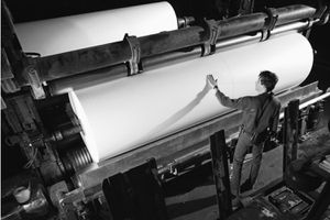 Man inspecting roll of paper in mill,