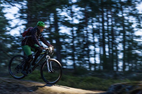 Woman riding bike in the woods at dusk