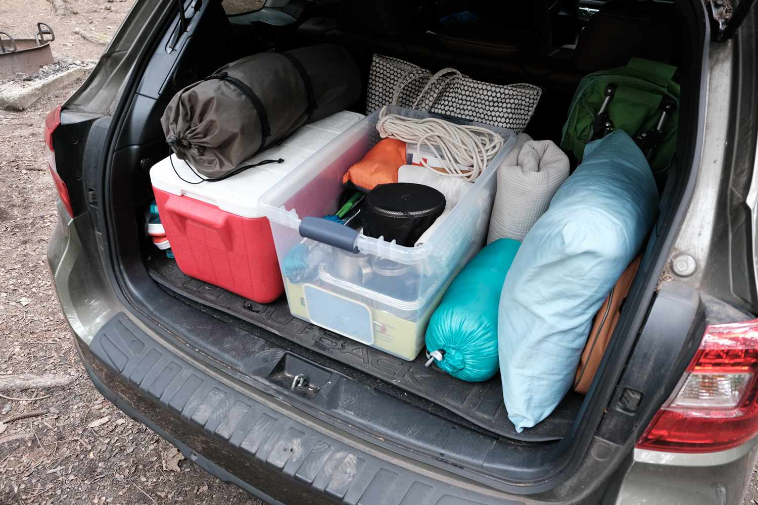 camping gear and coolers are neatly stacked into back of car