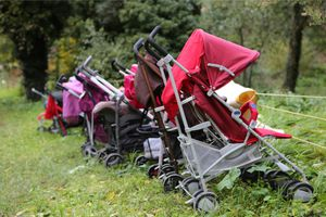 Several strollers parked in the grass