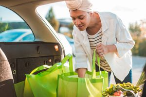 Woman loading her groceries into her trunk in reusable shopping bags