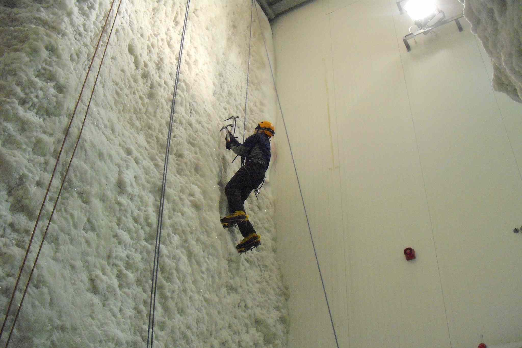 Climber scaling a human-made ice wall inside Scotland's Ice Factor