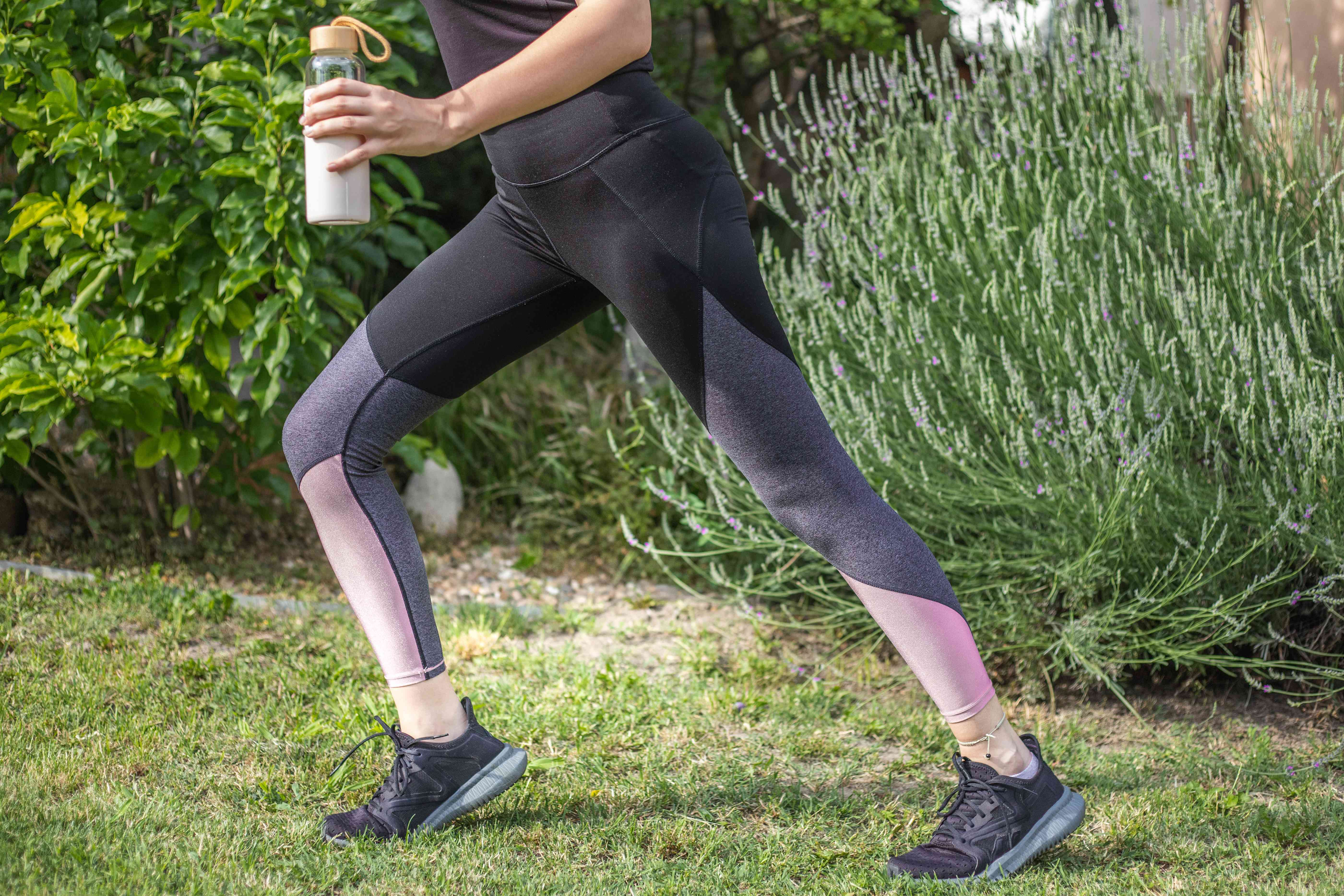 person in color-blocked leggings and workout shoes with water bottle stretches outside