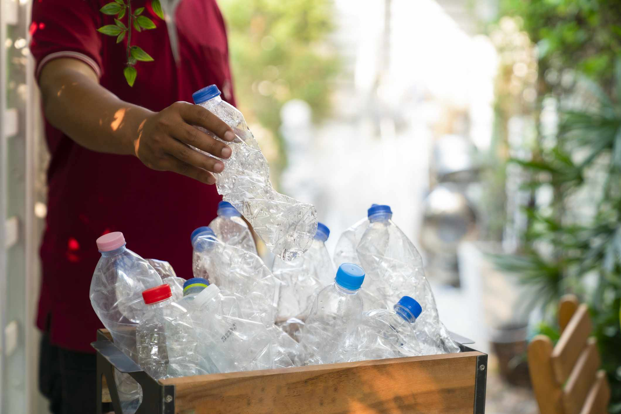 A man putting plastic bottles in a bin.