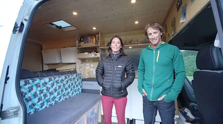 couple smiling from inside their camper van