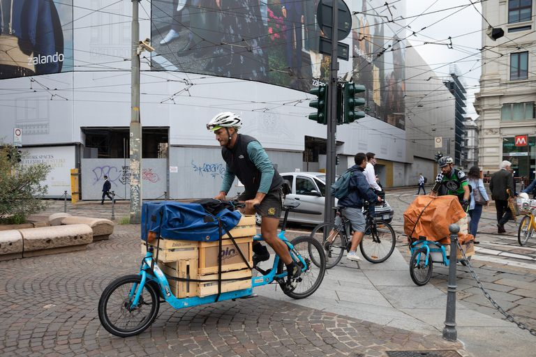 Two cycle couriers ride their cargo bikes as they deliver food.