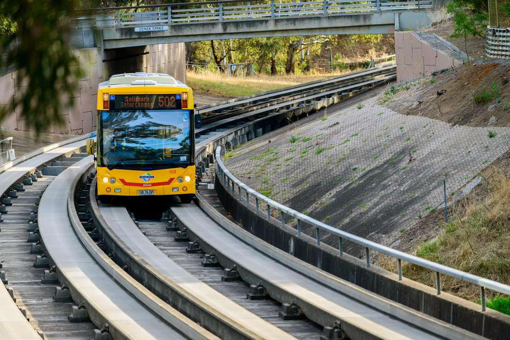 Yellow O-Bahn bus traveling on the dedicated busway tracks