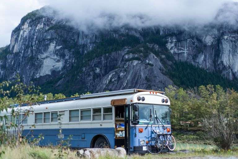 Bus with bikes on front rack parked near a mountain
