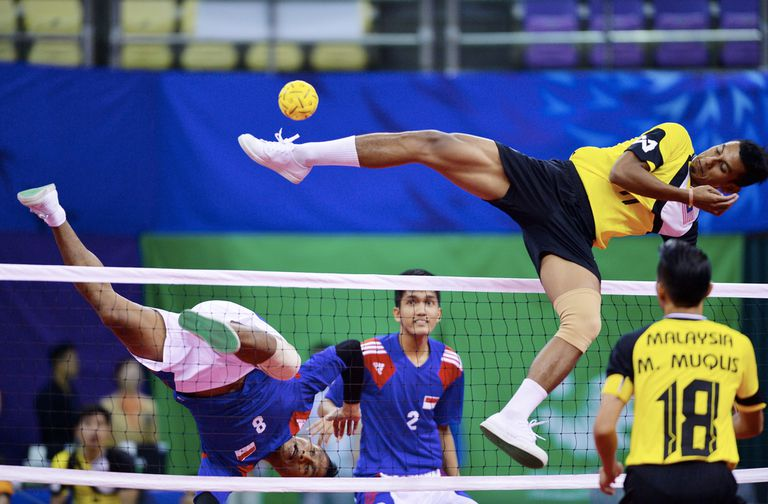 Sepak Takraw players in the middle of a game
