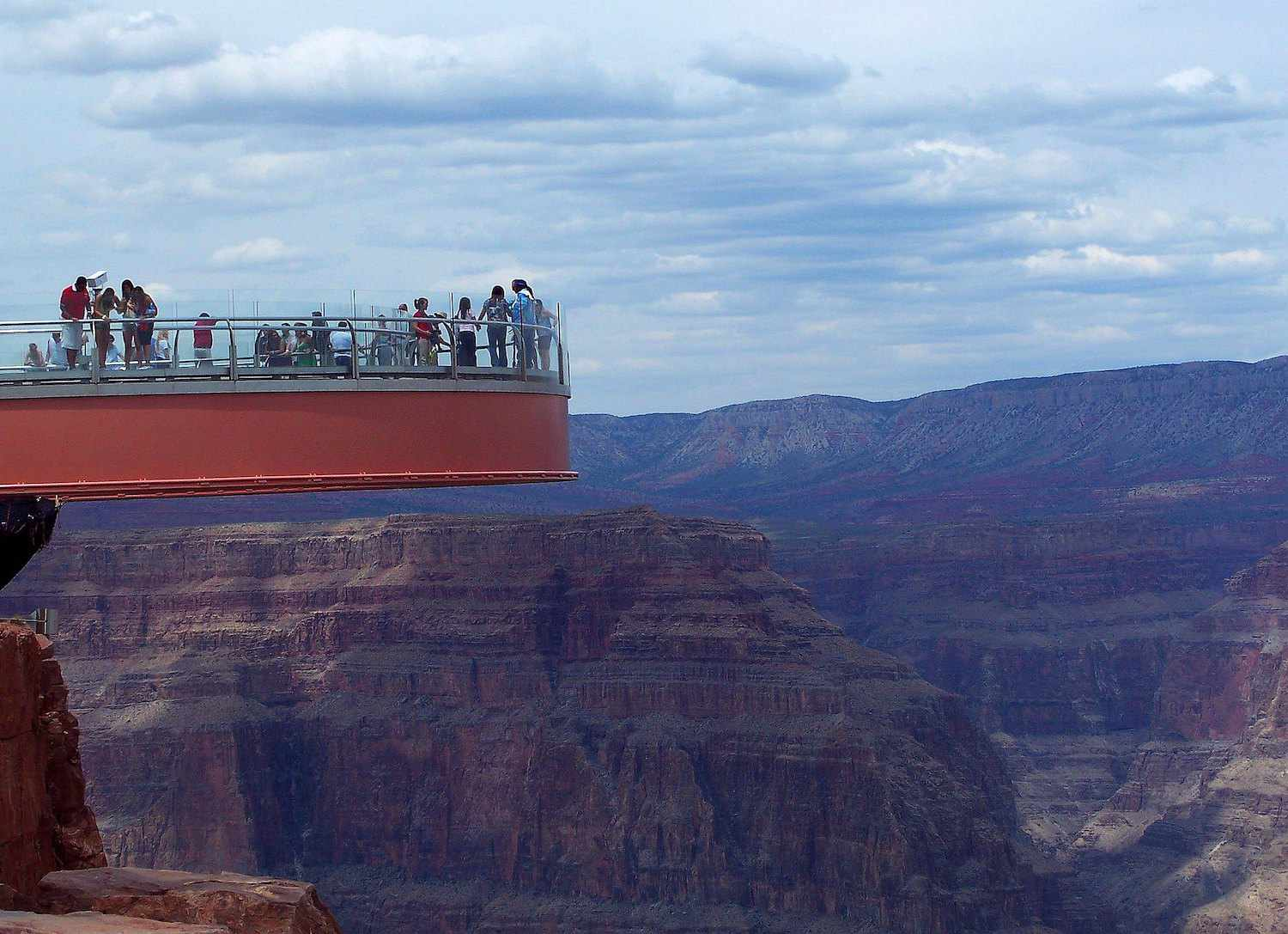 Visitors look out from the Grand Canyon Skywalk out to the canyon below.