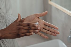 Person applying moisturizer to their hands