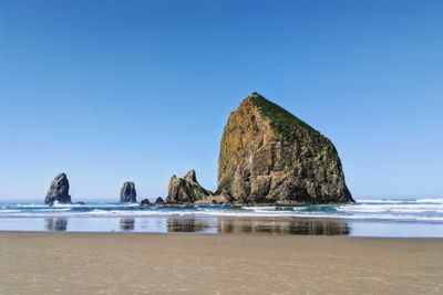 A large rock monolith in the surf on a sandy beach