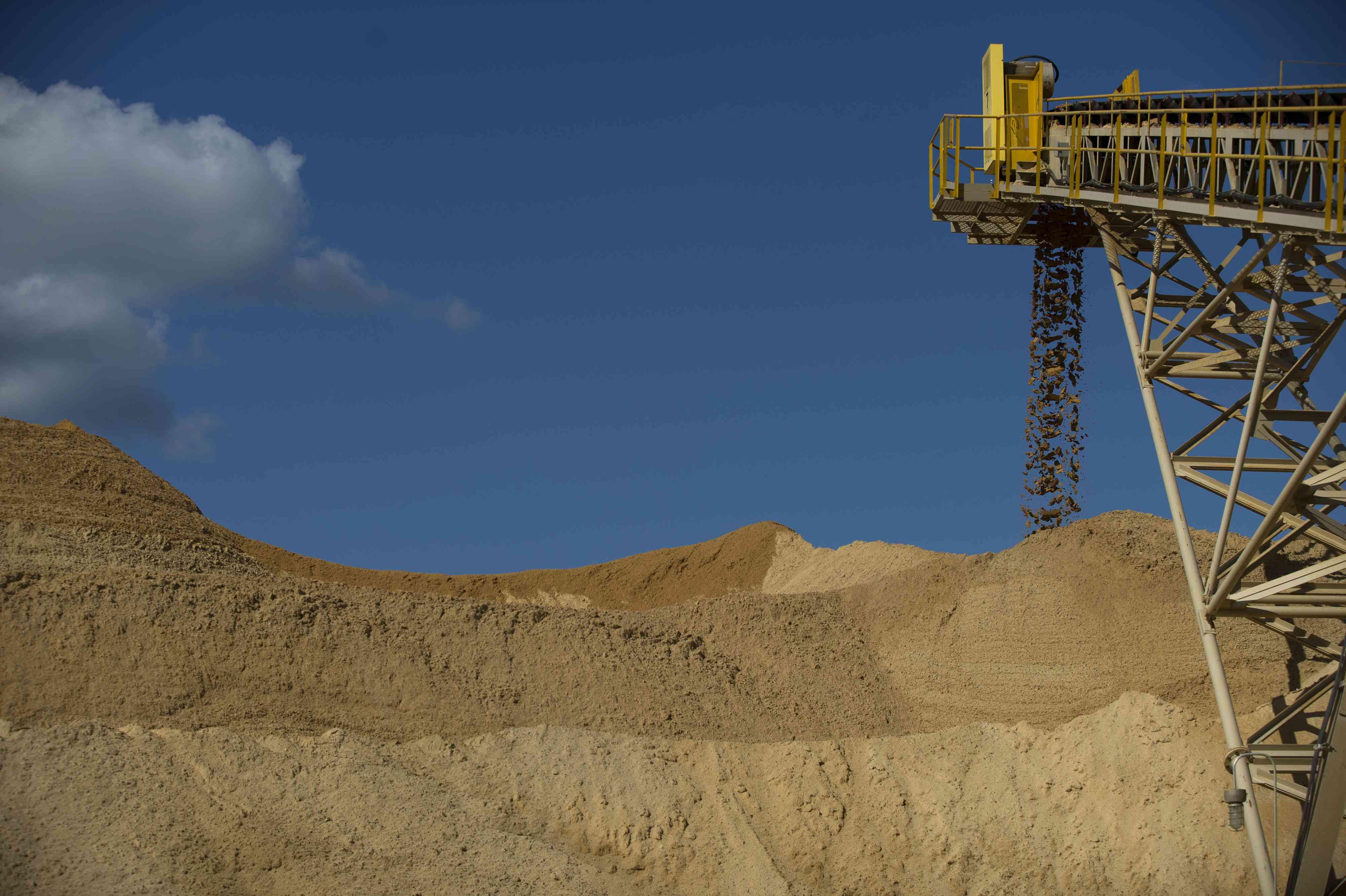 A conveyor belt dumps raw sand into a pile
