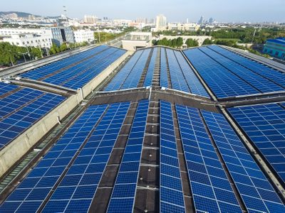 Solar panels on a roofs overlooking a city landscape.