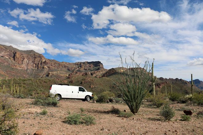 Van parked in the desert with mountains in the background