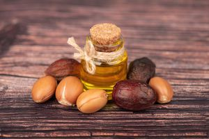 Argan oil, on wooden background. Argan nuts and seeds, for cosmetic and beauty products. Natural argan fruit from Morocco.