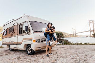 Couple having fun outside of a campervan