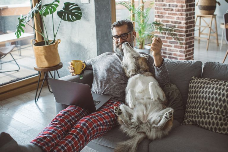 Image of a man and dog sitting on a couch together